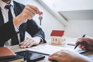 fastighetsmäklare som ger husnycklar till klienten foto