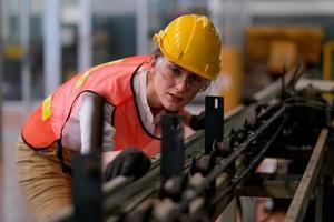 ung kvinnlig tekniker på industriellt arbetsgolv foto