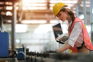 kvinnlig tekniker som gör fabriksarbete foto