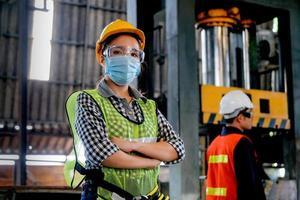 kvinnlig fabrikstekniker som poserar på jobbet