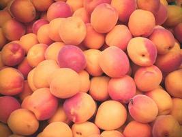 hög med färska mogna persikor till salu på marknaden. foto