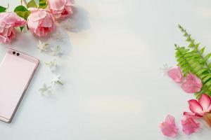rosa blommor med ormbunkar och smartphone