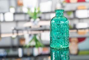 grön glasflaska på bordet