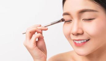 asiatisk kvinna applicera ögonskugga