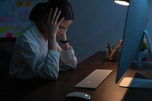 kvinna stressade att arbeta sent på natten foto