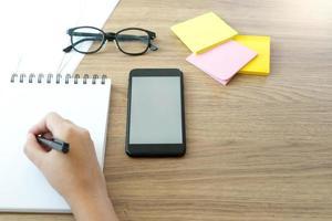 närbild av en hand som skriver vid skrivbordet foto