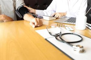hälso-och sjukvårdspersonal tar en blodtrycksavläsning foto