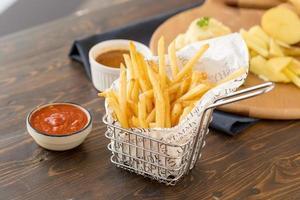 pommes frites med ketchup på träbord foto