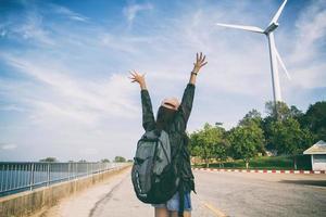 kvinna som står med upphöjda armar med ryggsäcken på foto