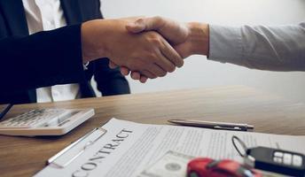 klienten skakar hand med bilförsäljaren