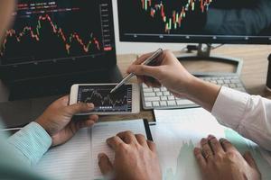 två investerare arbetar tillsammans för att analysera grafer