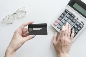 närbild av kvinna som håller kreditkort och använder miniräknare foto