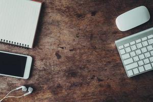 platt låg skrivbord med elektroniska enheter och anteckningsbok foto