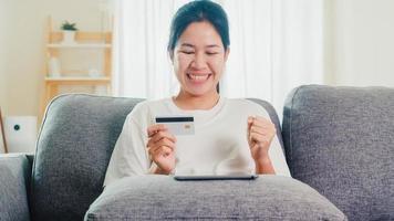 asiatisk kvinna som använder surfplatta och kreditkort i vardagsrummet.