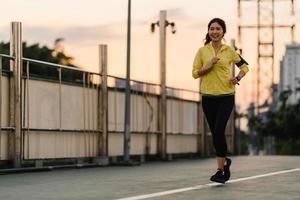 ung asiatisk idrottsman nen som kör på en gångbro utomhus