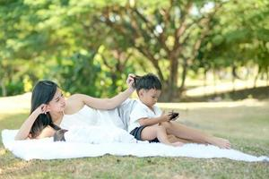 ung familj kopplar av i en park foto