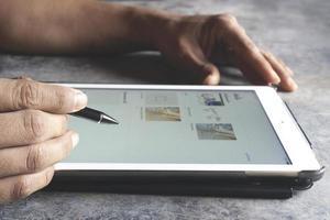 närbild av en affärsman som använder mobil surfplatta foto