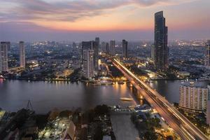 bangkok stad vid solnedgången med trafikljusspår foto
