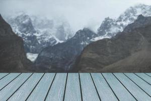 träplankor mot snötäckta bergskedja foto