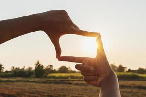 närbild av en hand som inramar solnedgången foto