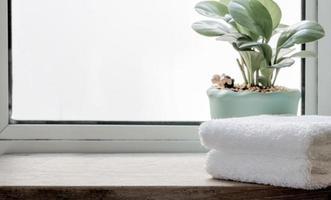vikta rena handdukar med krukväxt på träbord foto