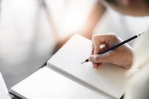 manhand skriver på anteckningsboken med penna