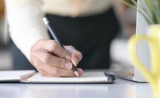 en hand som skriver på anteckningsboken med penna