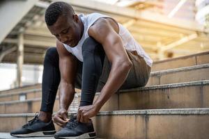 närbild av en ung modell idrottsman snörning sneakers foto