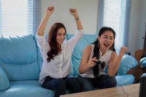 asiatiska kvinnor som spelar videospel hemma foto