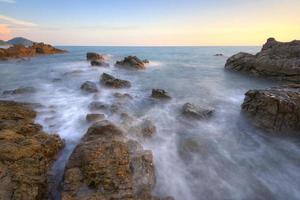 lång exponering av en stenig strand foto