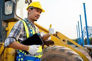 byggnadsarbetare intill grävlastare foto
