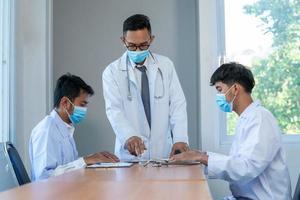 män i labbrockar vid mötesbordet foto