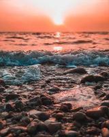 stenar och vågor på stranden med färgglad himmel foto