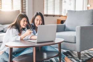två glada asiatiska kvinnor som skrattar medan de arbetar med laptop hemma foto