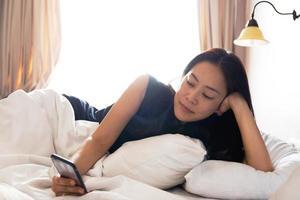 kvinna kopplar av med telefonen på sängen foto
