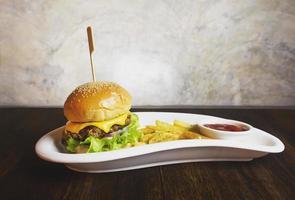 cheeseburger och pommes frites på den vita plattan foto