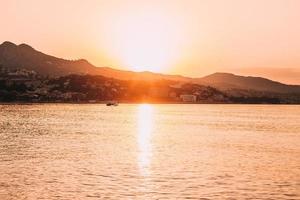 silhuett av båt på havet under solnedgången foto