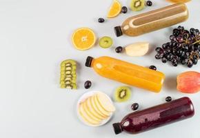 flaskor juice och olika frukter foto