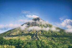 grönt berg under blå himmel foto