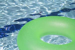 grön uppblåsbar flytning i poolen foto