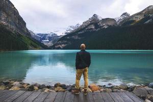 man i blått stående vid de kanadensiska klipporna foto