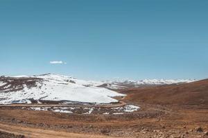grusväg i vildmarkens bergsområde mot klar himmel foto