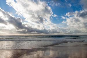 strand med vågor och molnig blå himmel foto