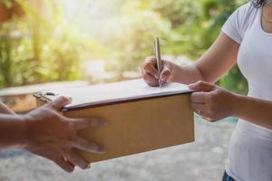 kvinna undertecknar för leverans foto