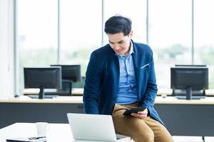 glad ung asiatisk affärsman på kontoret