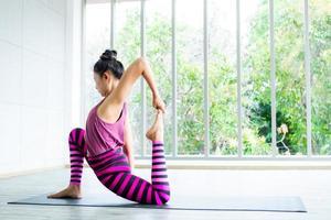 asiatisk kvinna som gör ett stretchingträning foto