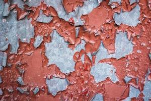närbild av väggen med skalande röd färg foto