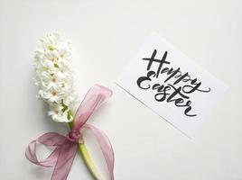 lyckligt påskskylt med vita blommor foto