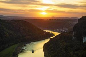 båt går nerför floden under solnedgången. foto