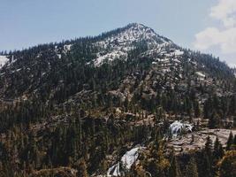 berg med gröna träd under blå himmel foto